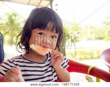 Little asia girl wakes up on the morning. She eating toast with strawberry jam. little asia girl has happy and good healthy when to eat a breakfast.
