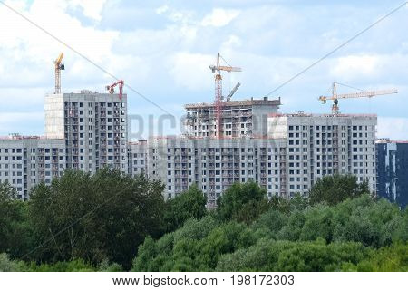 City construction. Landscape with cranes and new block of flats construction in new green ecological district sky with white clouds in summer day