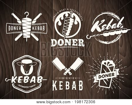 Doner kebab logos. Vector kebab badges with traditional eastern grill dishes on the wooden background. Vintage labels for restaurant or bar.