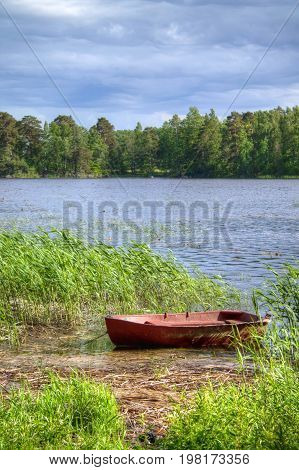 Old fishing boat in the reeds at fising lake