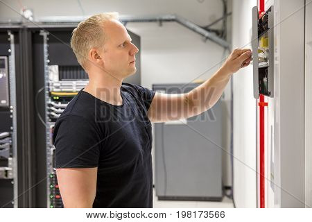 Side view of confident male technician opening fire panel in datacenter