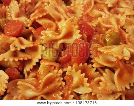 bowtie pasta with tomato sauce, tomatos, and olives