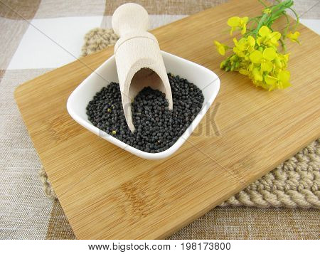 Fresh rapeseed and rapeseed flower on a wooden board