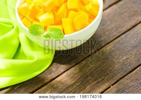 Mango slice or mango diced in white bowl on old wooden background