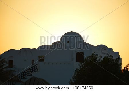 Sunset at Egypt with silhouette of Nubian town.