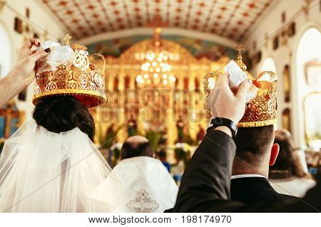 Wedding Ceremony Bride And Groom In The Orthodox Church. Witnesses Hold Crowns Over The Heads Of The