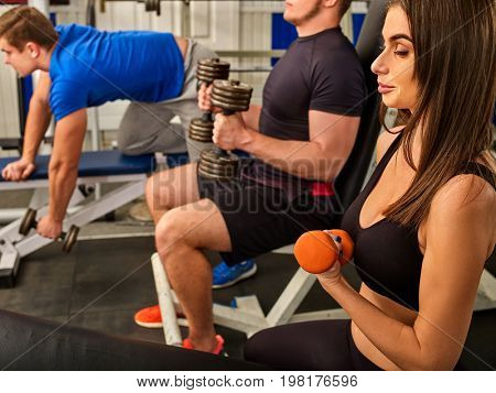 Friends in gym workout with fitness equipment. Fitness training women and men follow instructions of the coach. Girl wants to keep herself in good shape.