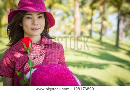 Happy Young Woman With Holding Roses And Teddy Bear In The Coconut Park.