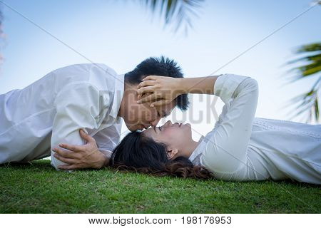 A Pair Of Lovers In The Park With Man Kissing Young Woman On The Grass.