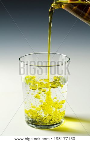 Physics. Immiscible fluids. Oil being poured into water. 1 of 4 image series.
