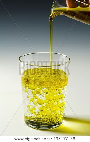 Physics. Immiscible fluids. Oil being poured into water. 3 of 4 image series.