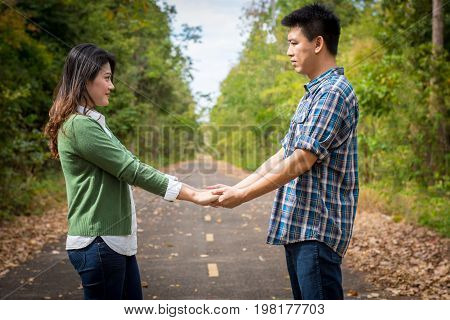 Beautiful Young Couple With Green Coats Walk Hand In Hand On The Road.