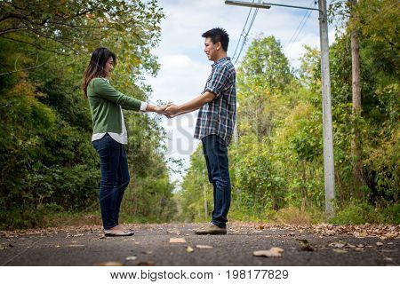 Couple Holding Hands On A Forest Road.