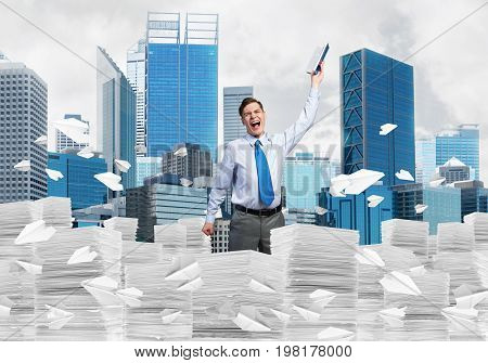 Businessman keeping hand with book up while standing among flying paper planes with cityscape on background. Mixed media.