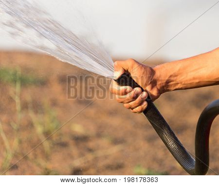 Man watering the lawn with a hose .