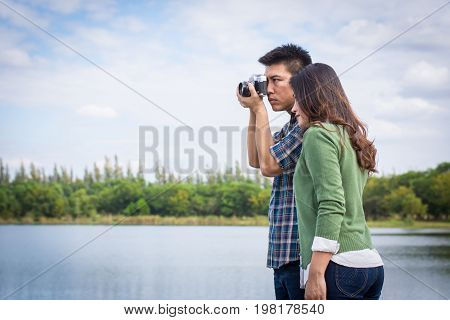 Young Men And Young Women Couple Together Standing On Bench Waterfront Port In The Park. Handle Vint