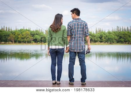 Beautiful Young Couple With Green Coats Standing Hand In Hand On Bench Waterfront Port In The Park.