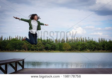 Woman Jumps With Arms Raised On A Bench By The Pool.