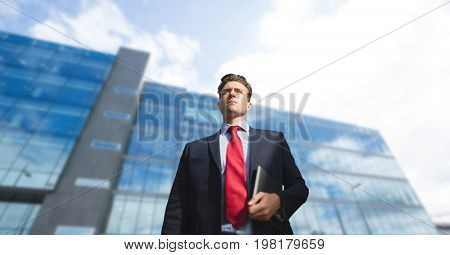 Digital composite of Business man standing against building background