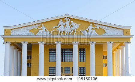 The pediment of the theater with the barrels on the background of the blue sky