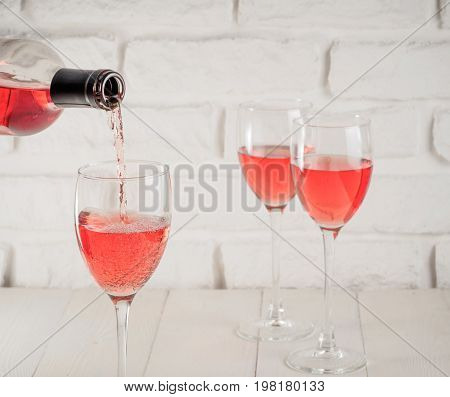 Pouring pink wine from bottle into wineglass on white brick wall background. Two wineglass with rose wine on background. Copy space.