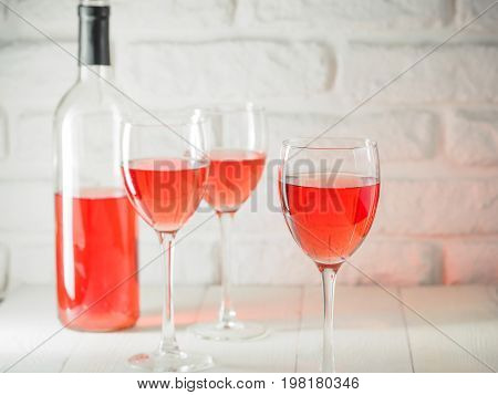 Three wineglass and bottle of pink wine on white brick wall background. Rose wine in wineglass. Copy space.