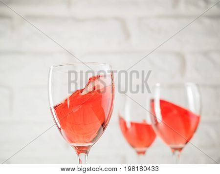 Three wineglass with pink wine on white brick wall background. Splashes rose wine in wineglass. Copy space.