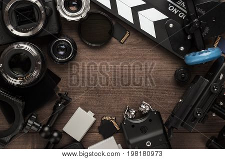 top view of different video making equipment. video making equipment on brown wooden table with copy space. indie movie production and video making essentials. video making tools on a table forming frame