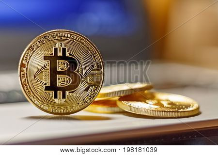 Golden Bitcoins On The Laptop Touchpad Closeup. Cryptocurrency Virtual Money