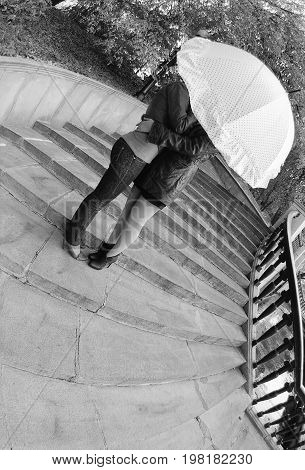 Moscow Russia September 16 2012: Two girls hug under an umbrella on the stairs. Attention! The image contains the graininess of the photographic film!