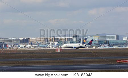 FRANKFURT, GERMANY - FEB 28th, 2015: Gate and terminal buildings at Frankfurt International Airport FRA with varios planes in the foreground.