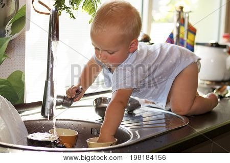 Cute Toddler Boy Washing Dishes In Domestic Kitchen. Adorable Baby Boy Playing With A Water Faucet