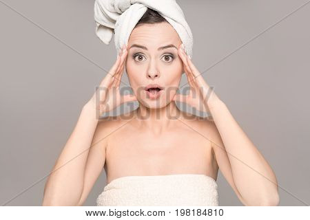 Shock and surprised - portrait of a beautiful young woman. Open mouth with surprise. Copy space on a gray background. Topics of beauty and spa.