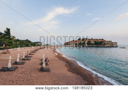 Sveti Stefan island and beach near Budva, Montenegro on Adriatic coast. Evening view of Adriatic sea, St. Stefan luxury fortificated village and private beach.