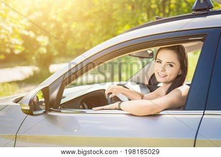 Beautiful young woman sitting in the interior of a new car with a smile. He is glad he is a driver.