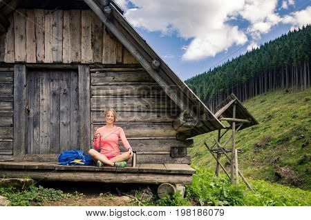 Girl camping and hiking drinking coffee or tea in beautiful Tatra mountains on hiking trip. Inspirational landscape in Poland. Active woman resting outdoors in summer nature.