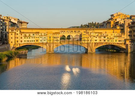 Ponte Vecchio bridge over the Arno River in sunset light, Florence, Italy. The bridge first mention was in a document of 996. One of the main attractions of Florence.