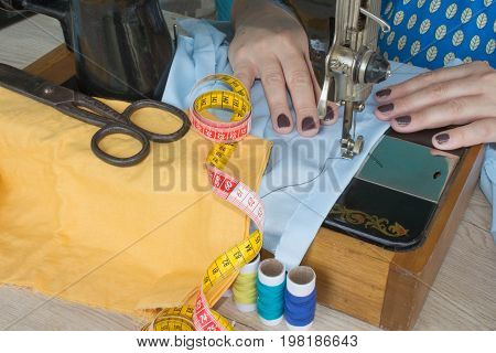 processes of sewing on the sewing machine sew women's hands sewing machine. sewing machine and female scissors