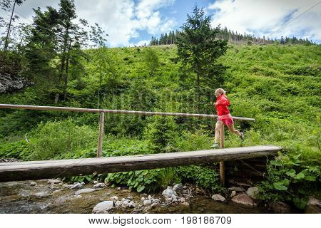 Young girl running in mountains on summer sunny day. Female trail runner crossing bridge on a mountain river. Sport and fitness concept outdoors in nature.