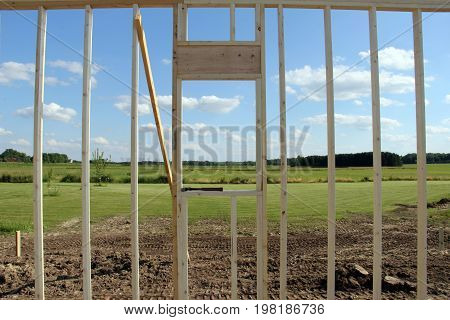 Rural country landscape seen through the frame of a new house construction