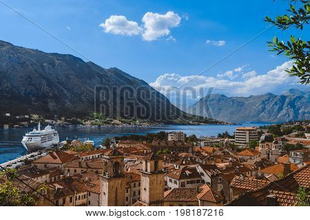 Kotor Bay and Old Town panorama from above Kotor's castle of San Giovanni. Mountains, traditional house roofs and Boka Kotorska fjord wide angle view.