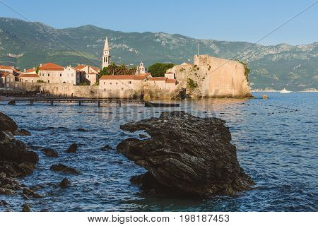 Budva Old town wall, St.John church spire, mountains, St. Nicholas island and Adriatic sea view. Tourist capital Budva by evening.