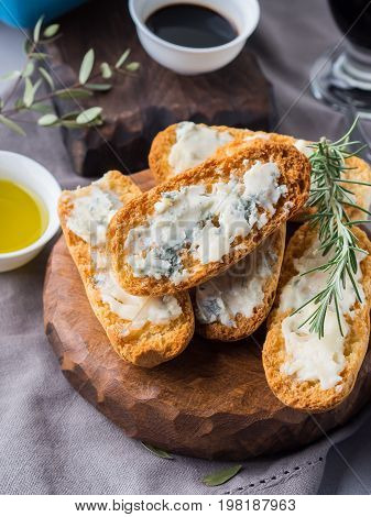Italian toasts with gorgonzola cheese on rustic background with wine