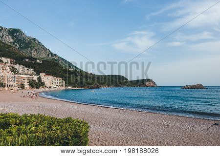 Public beach near Sveti Stefan island, Montenegro. Pebble beach and coastline with resorts near Budva.