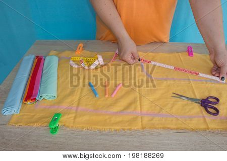 Tailor woman working in his tailor shop Tailoring. A tailor is laying out a dress/Sewing layout