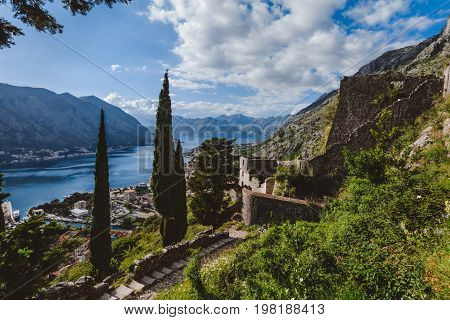Kotor fortress walls and stone staircase wide angle view with Kotor Bay, Old Town rooftops and cloudy mountains on background. Boka Kotorska, Montenegro.