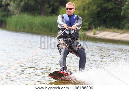 VATUTINE, UKRAINE - JULY 15: The athlete enjoys wakeboarding and coaches tricks on July 15, 2017 in Vatutine, Ukraine.