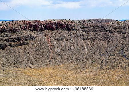 The Arizona desert was changed forever when a Meteor from space impacted the ground and created a crater almost a mile wide (0.737 mi) and 3900 ft. in diameter and the rim of the crater is elevated 148 ft above the surrounding desert amazing.
