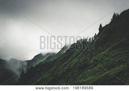 Moody storm clouds shroud a mountainous, rugged landscape in thick fog.