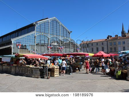 NIORT, FRANCE, JULY 16 2017: View of the colorful Sunday local produce market and Place de Halles in Niort, a town in the Deux-Sevres region of western France. Popular with both tourists and locals.